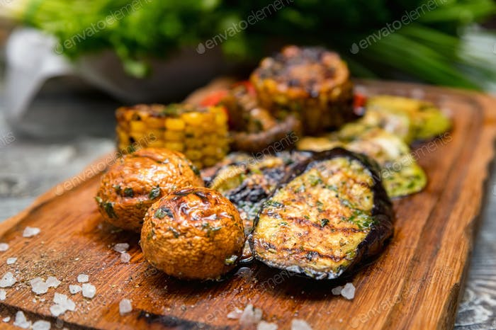 Various tasty grilled vegetables and mushrooms on rustic background