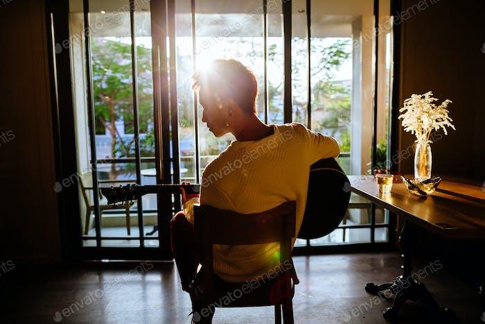 asiatische künstler mann spielen gitarre in cafe sonnenlicht