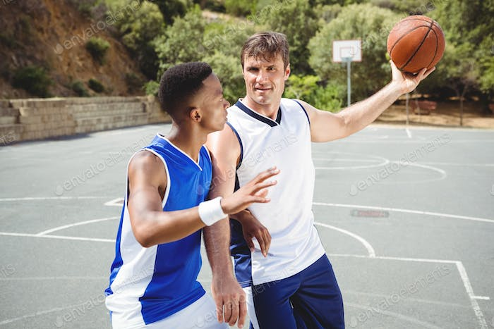 Confident players playing basketball