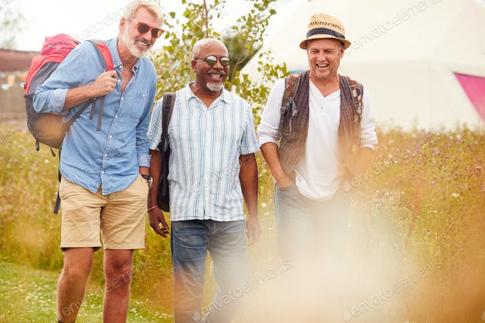 Group Of Mature Male Friends Walking Along Path Through Yurt Campsite