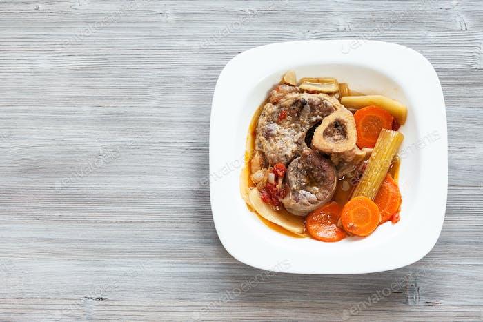 italian dish Ossobuco in white plate on gray board
