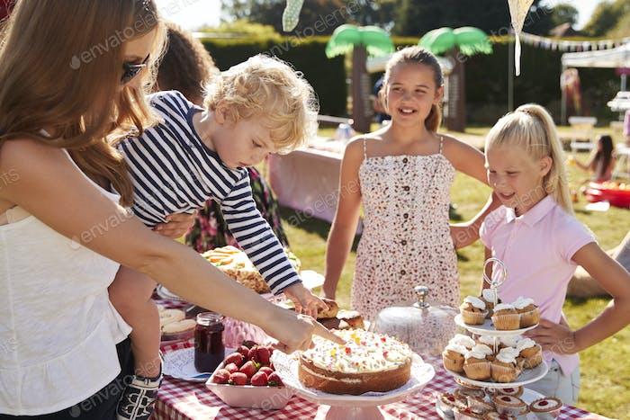 Children Serving On Cake Stall At Busy Summer Garden Fete