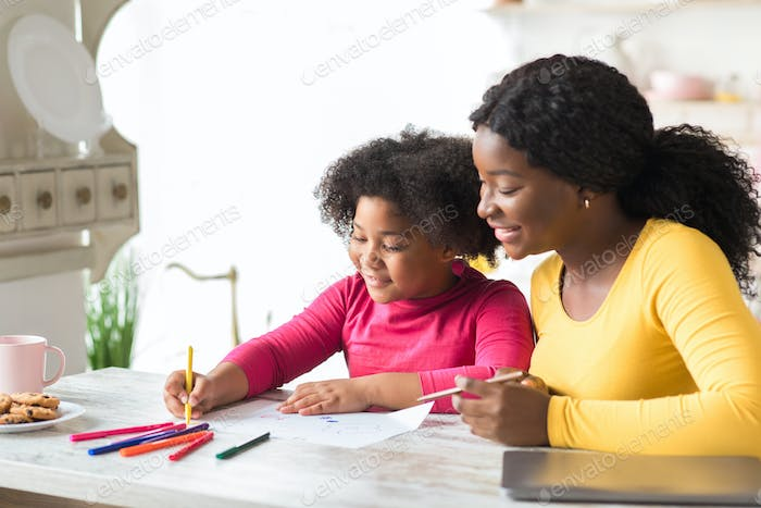 Happy Black Mother And Cute Little Daughter Drawing Together At Kitchen Table