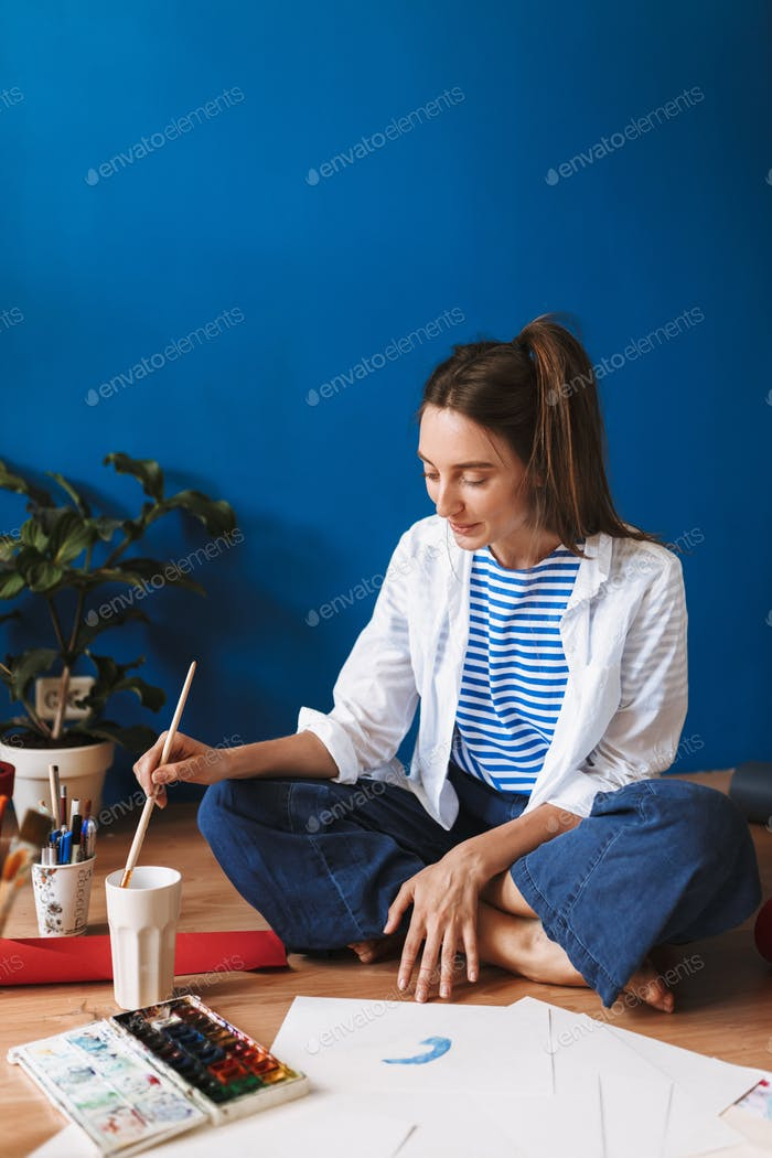 Young smiling painter in white shirt and striped T-shirt sitting