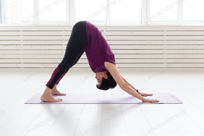 Yoga, people concept - a middle-aged woman doing a yoga and try to do a asana