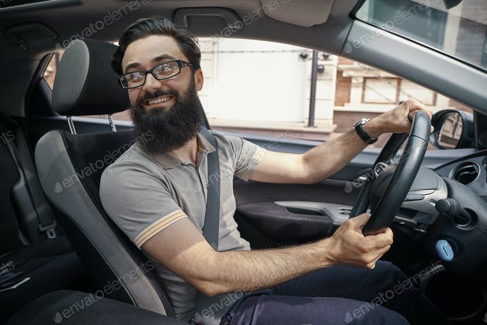 Handsome, happy man driving the car