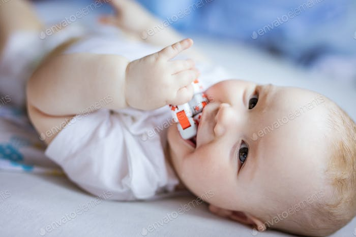 Cute baby girl playing with toy, looking at camera and smiling