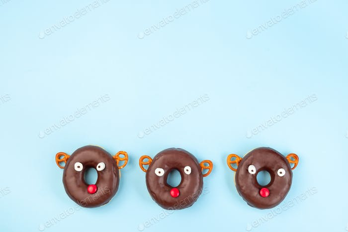Three Christmas reindeers made from chocolate doughnut, pretzel cookie, marshmallow and candy
