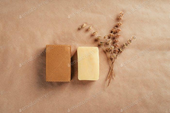 Stück Seife mit Rüschenkarton und trockenen Kräutern auf rustikalem Naturpapier