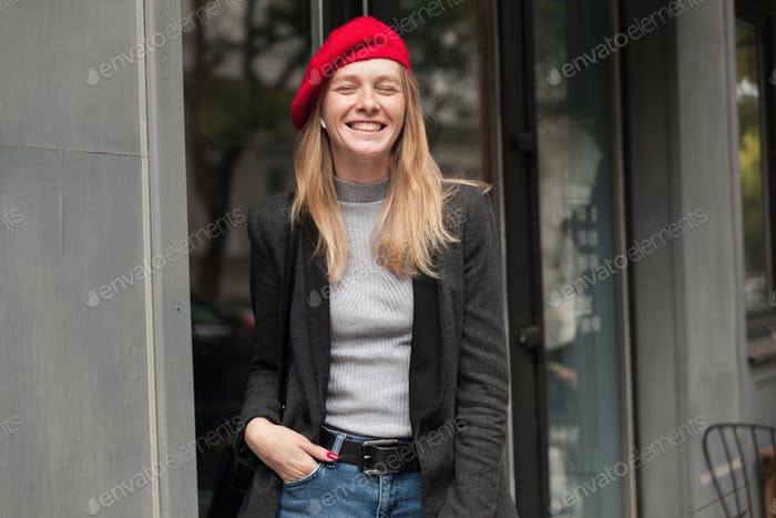 Pleasant looking young cheerful lady with blonde long hair dressed in trendy clothes and red beret