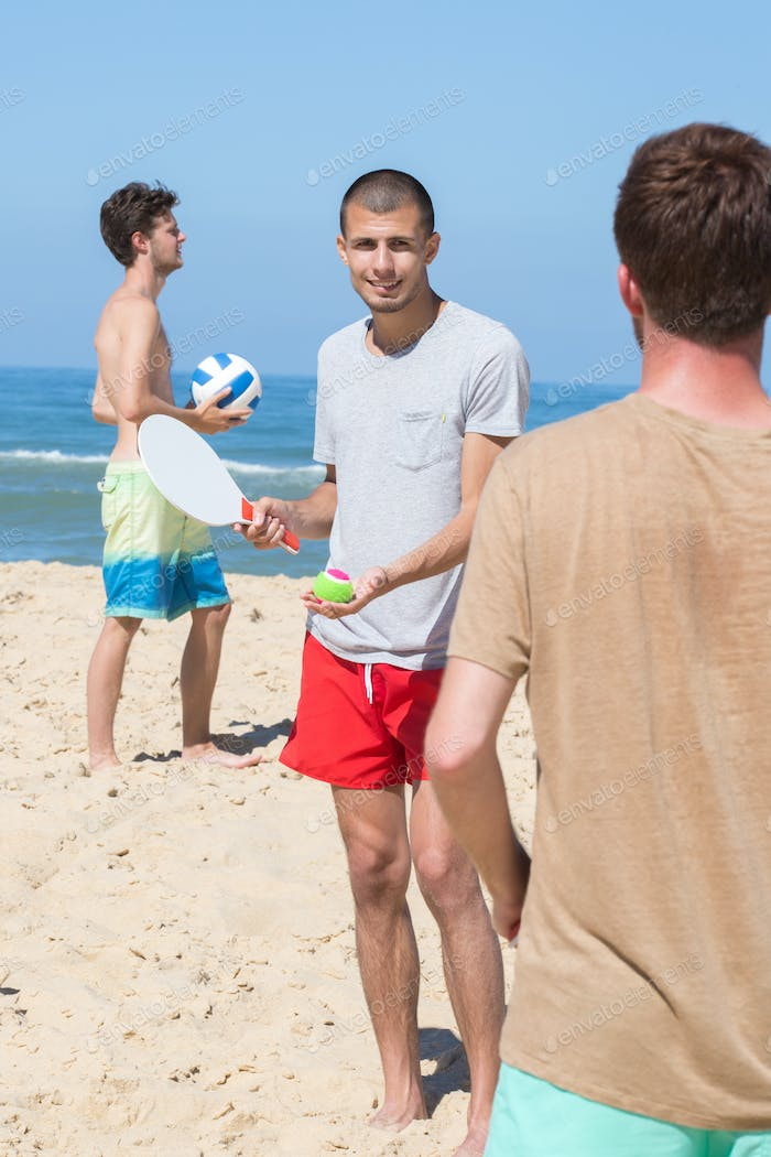cheerful happy friends relaxing at beach and playing with rackets