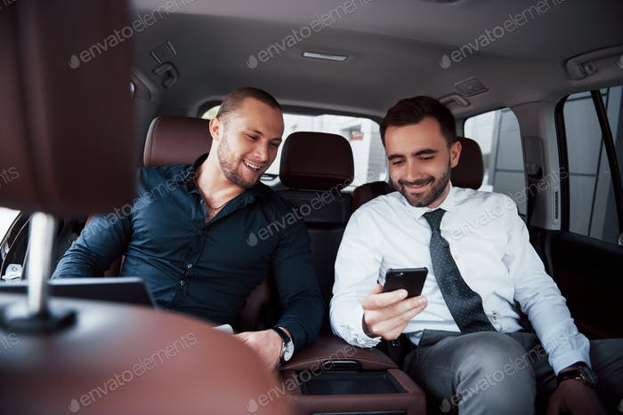 The two old business friends conclude a new agreement in an informal setting in the car's