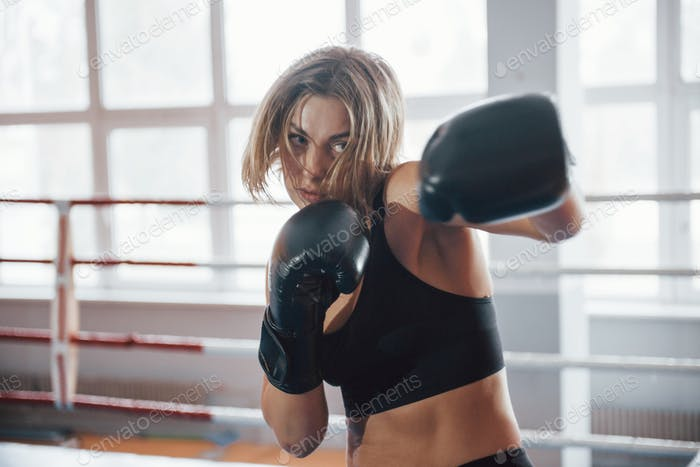 Shadow fighting. Female sportswoman training in the boxing ring. In black colored clothes