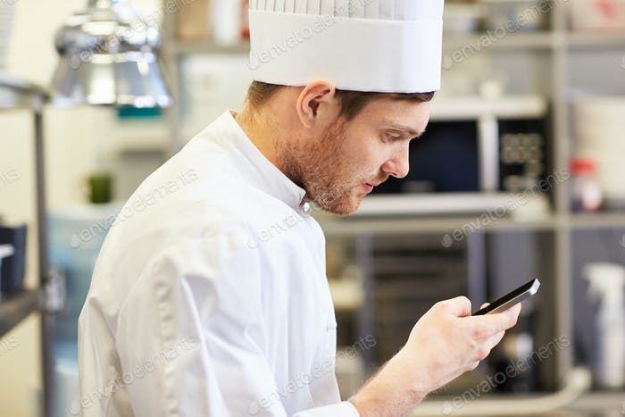 close up of chef with smartphone at kitchen