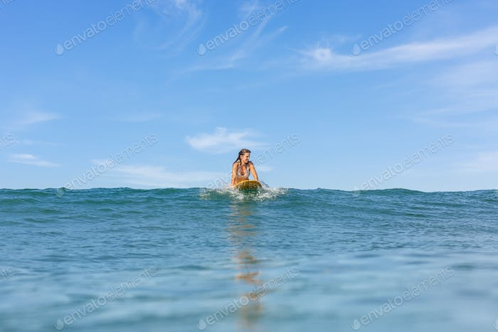 One beautiful sporty girl surfing in the ocean.