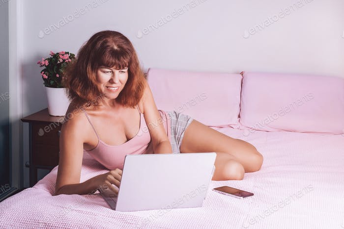 Happy middle age woman working at home on a laptop sitting on the bed in the house.