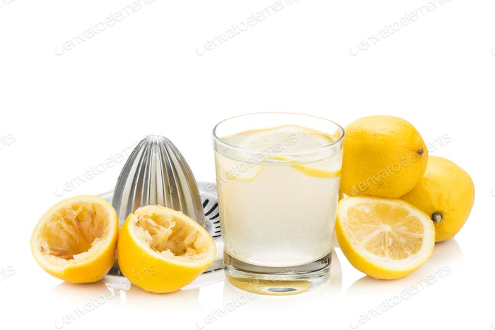 Freshly squeezed organic lemon juice with glass and squeezer.