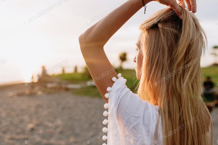 Romantic sensitive young woman with long blond hairs from behind posing on the sunny beach.