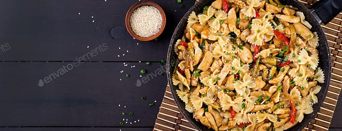 Stir fry chicken, pasta farfalle, zucchini, sweet peppers and green onion. Top view. Asian cuisine