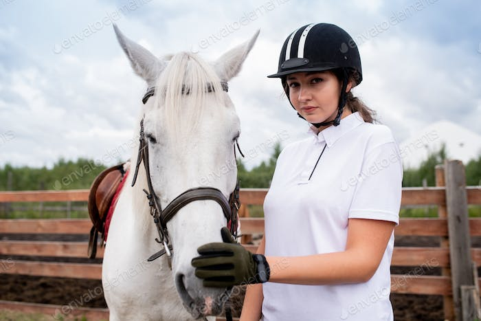 Pretty girl in equestrian helmet and gloves touching nose of white racehorse