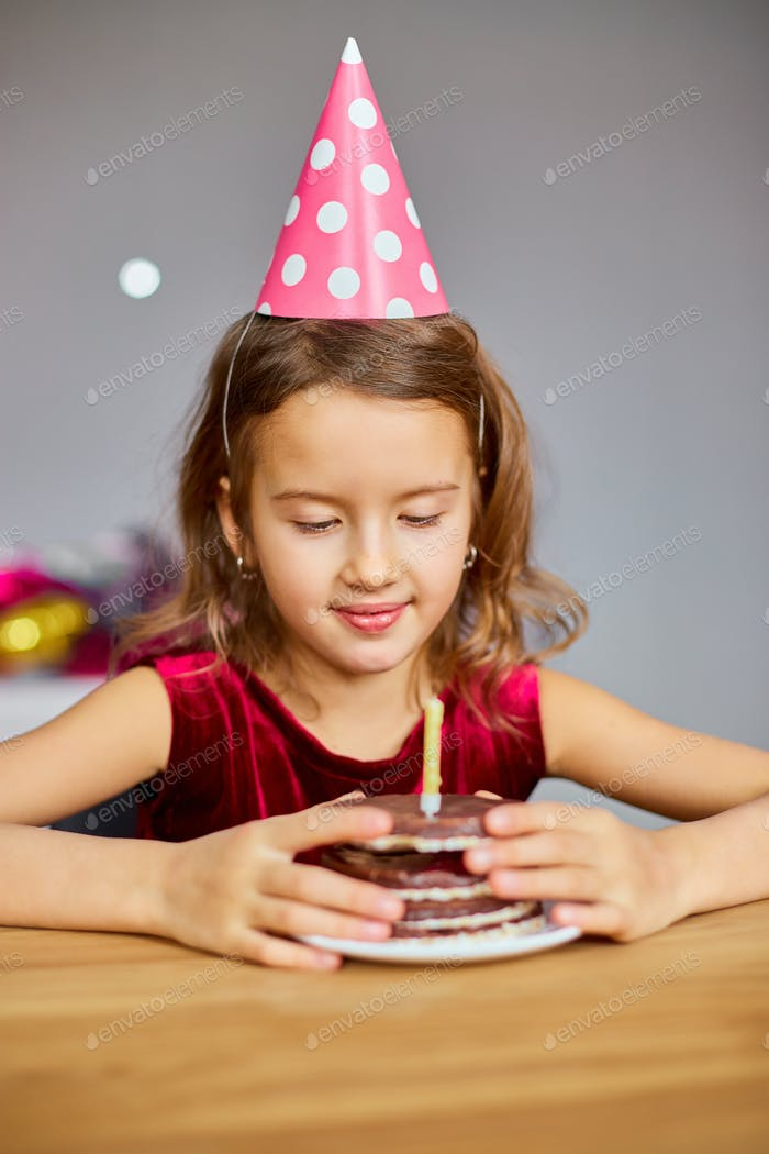 A little girl is wearing a birthday hat looking at a Birthday Cake