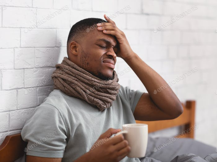 African Man Touching Forehead Having Fever Sitting In Bed Indoor