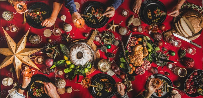 Flat-lay of friends celebrating Christmas over festive table, top view