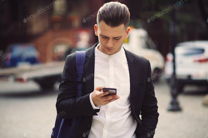 Junger Mann mit Rucksack hält ein Telefon