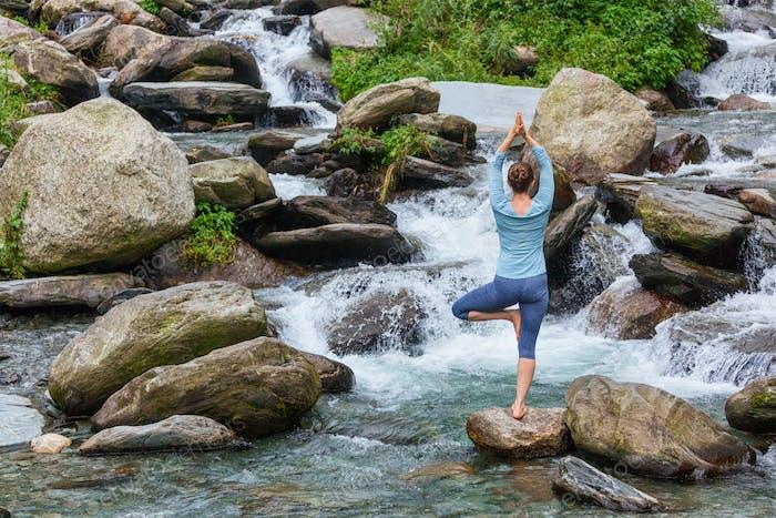 Frau im Yoga Asana Vrikshasana Baum Pose am Wasserfall im Freien