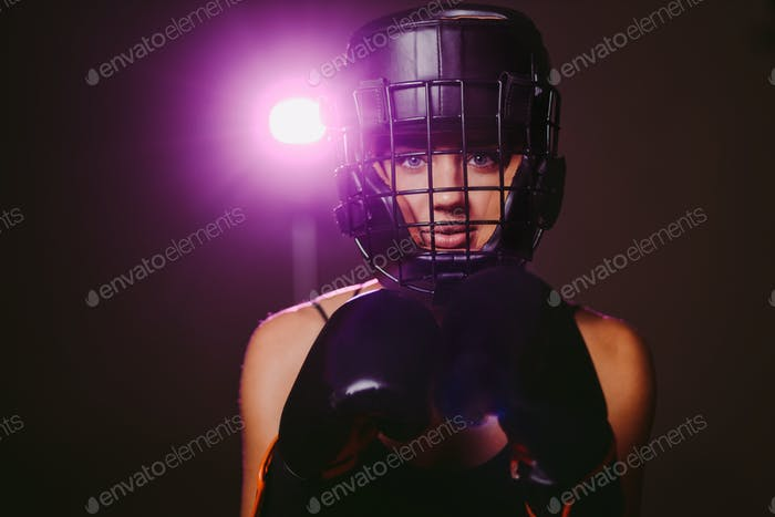 sexy woman fighter in boxing gloves and headgear portrait