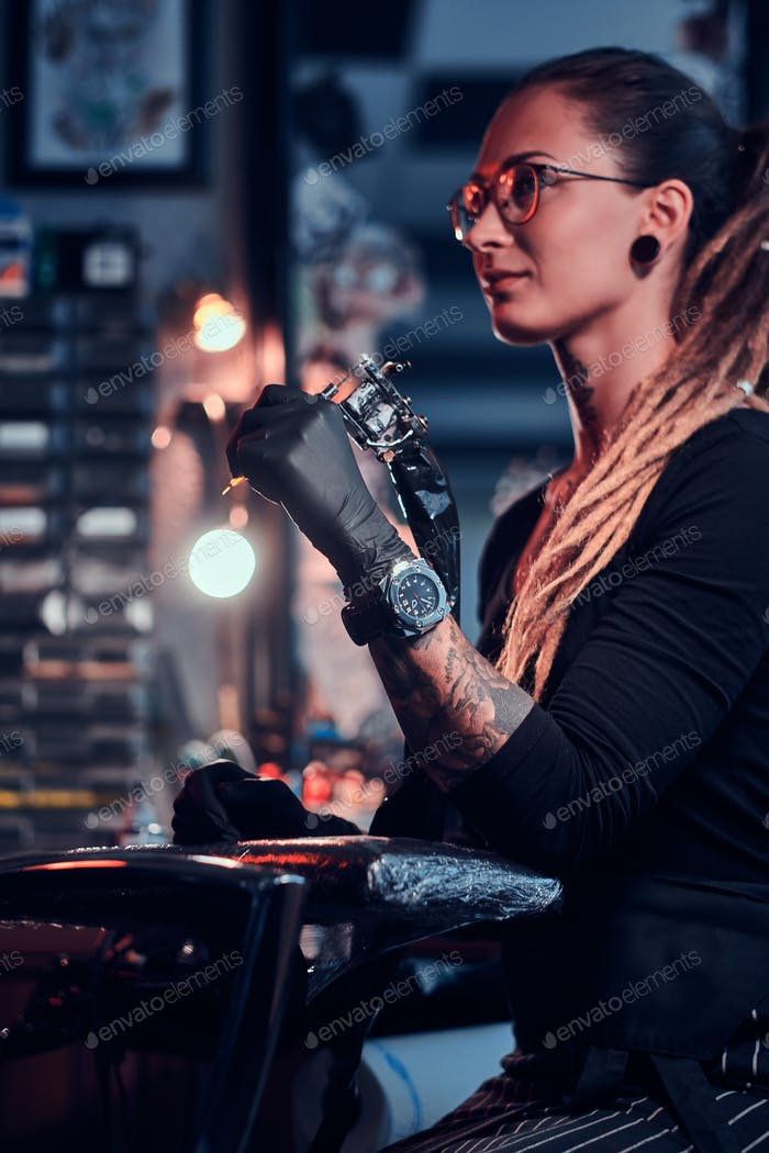 Portrait of attractive young woman with tattoo machine in hands