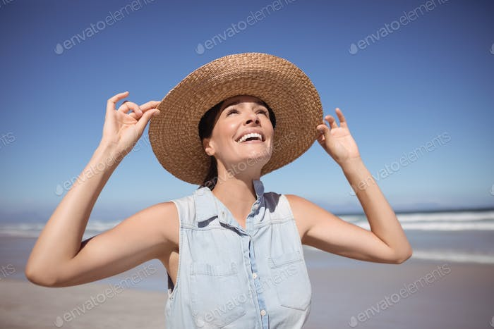 Happy woman wearing sun hat at beach