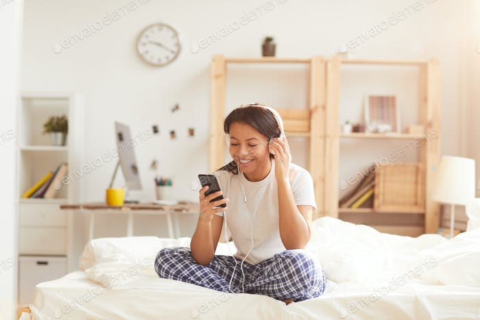 Young Woman Listening to Music on Bed