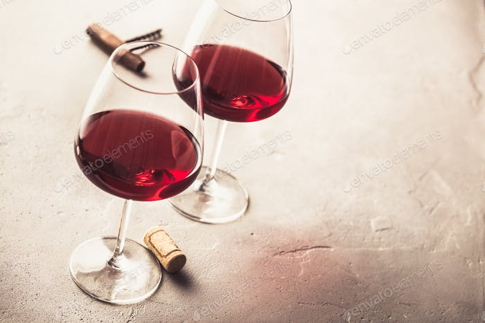 Glasses of red wine on concrete background, copyspace