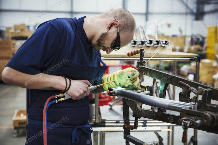 Männlicher Facharbeiter, der Teile eines Fahrrades in einer Fabrik schweißen.