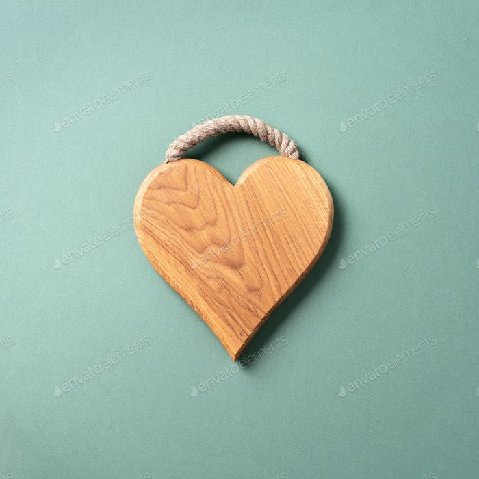 Heart shaped cutting board over blue and green background. Top view. Copy space. Valentines day