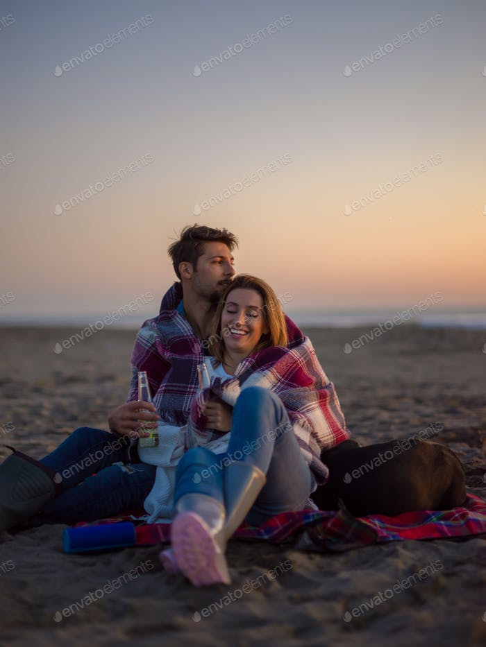 Loving Young Couple Sitting On The Beach beside Campfire drinkin