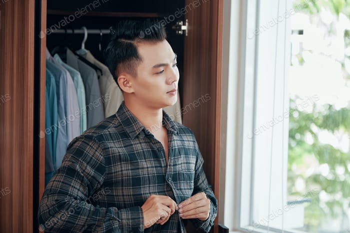 Relaxed young man dressing in morning