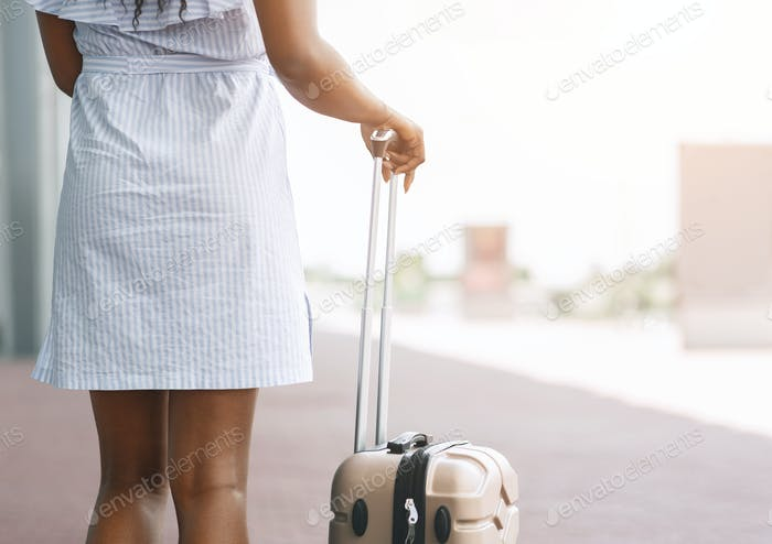 Black millennial woman standing with luggage at airport