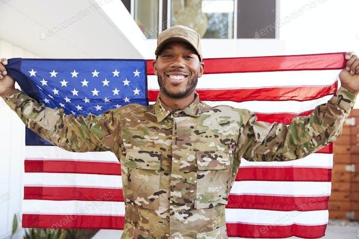 Millennial black soldier standing outside modern building holding US flag, Smiling