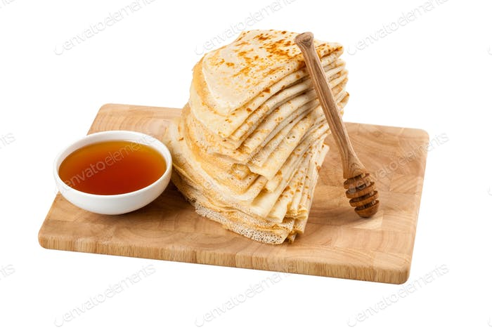 Homemade pancakes and honey on wooden board on white background