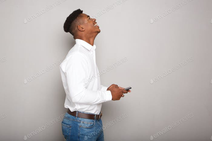 happy young black man holding cellphone by gray wall