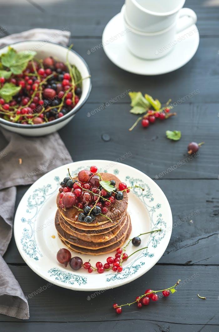 Breakfast set. Buckwheat pancakes with fresh berries and honey