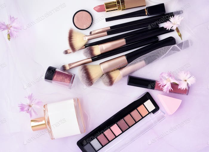 Makeup brush and decorative cosmetics with flowers on a pink vei
