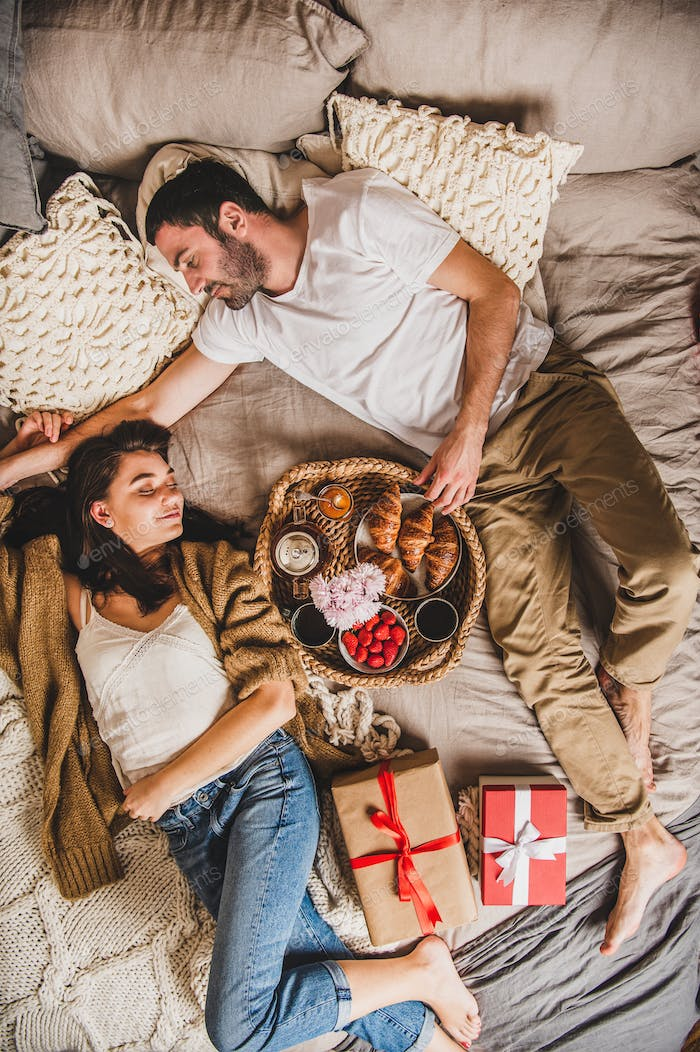 Happy smiling couple lying in bed and having festive breakfast
