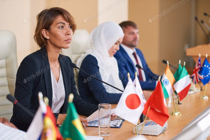 Young serious businesswoman in formalwear listening to speaker