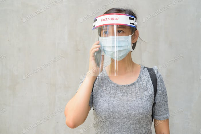 Young Asian woman talking on the phone with mask and face shield for protection from corona virus
