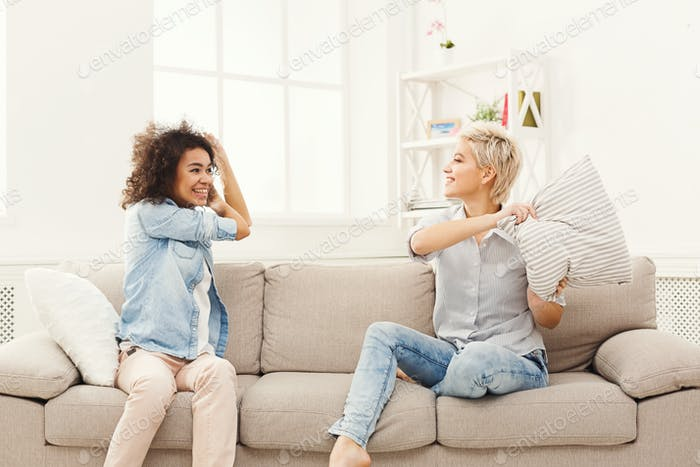 Two young women having pillow fight on sofa