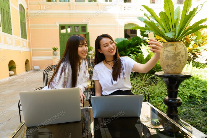 Two happy young teenage Asian women with laptop taking selfie together at the coffee shop