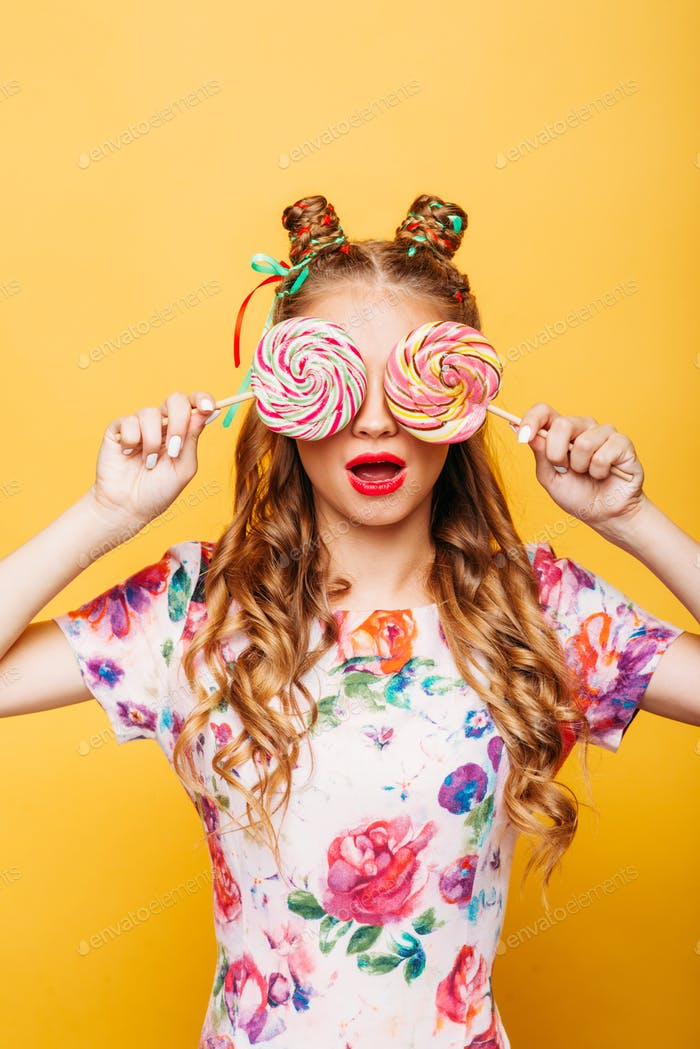 Young girl on the yellow background holding sweets